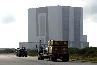 Flatbed trucks carrying some of the debris of Space Shuttle Columbia approach the Vehicle Assembly Building (VAB). The debris is being transferred from the Columbia Debris Hangar to the VAB for permanent storage. More than 83,000 pieces of debris were shipped to KSC during search and recovery efforts in East Texas. That represents about 38 percent of the dry weight of Columbia, equaling almost 85,000 pounds. Source: NASAPhoto Number: KSC-03PD-2613.