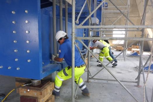 Amortisseur harmonique pour la Tour de Bakou:Quatre hommes déplacent le bloc de masse de 400 t pour mesurer la fréquence du pendule.