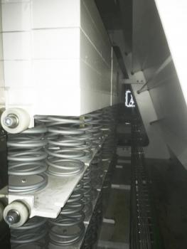 """Dachträger für das fahrbare Dach von Roland Garros : Blick in die """"Tiefe"""" – sprich: Länge – der Dachträger. Oben im Bild die langgestreckte schwingende Masse, unten die Federpakete, die individuell auf die Frequenzen der Träger justiert wurden. Die Schräge rechts resultiert aus der Geometrie der Stahlkastenträger. Das Licht in der Bildmitte rechts zeigt den nächsten Einstieg."""