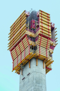 Als Außenschalung für den oberen Schaft wurde das Selbstklettersystem ACS R mit der VARIO GT 24 Träger-Wandschalung eingesetzt; die Wandschalung wurde dabei von der oberen Arbeitsplattform abgehängt. Dank dieser Sonderkonstruktion ließ sich die Schalung zurückfahren und die Arbeitsbühne nach oben klappen. Anschließend konnten Material und PERI UP Flex Bewehrungsgerüste per Kran von oben eingebracht werden.