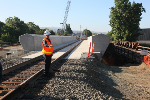 "Dave Cook, U.S. Army Corps of Engineers Sacramento District project manager for the Napa River-Creek Flood Protection Project, inspects a new railroad bridge in Napa, Calif., before its official opening June 22, 2011. The Sacramento District built the bridge to replace a lower adjacent railroad bridge that blocked the Napa River in high water, often causing flooding in downtown Napa. The project is part of the larger Napa River-Creek Flood Protection Project, a joint effort of the Corps, the city of Napa, and the Napa Flood Control and Water Conservation District to reduce flood risk for the city. ""The older bridges around here basically become a trash rack during high water flows,"" Cook said about accumulating debris. ""We relocated these tracks up and over so the water can make its way downstream a lot easier."" (U.S. Army Photo/Michael Nevins)"