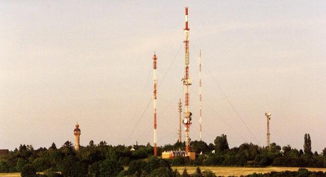 UKW- und Richtfunkmast Würzburg. Links ist der Hilfsmast der Telekom-Richtfunkstelle Würzburg-Frankenwarte zu sehen, dann folgen (von links nach rechts) der Mobilfunkturm Würzburg-Frankenwarte, der UKW- und Richtfunkmast Würzburg und der Sendemast des Bayerischen Rundfunks. Der Turm links von den Sendemasten ist der Aussichtsturm Würzburg-Frankenwarte