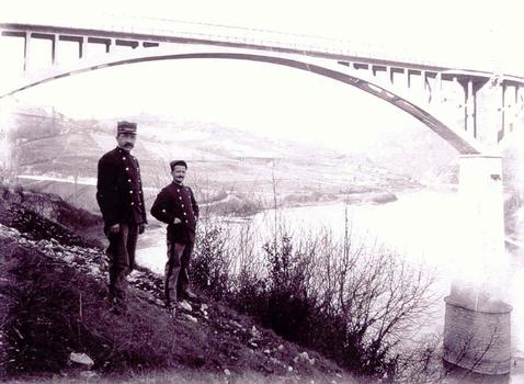Hommes uniformés devant le premier pont de Pyrimont (achevé en 1907)