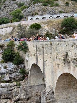 Saint-Jean-de-Fos - Pont du Diable vu de l'aval, la route et le canal de St Jean de Fos au second planDes jeunes plongent dans l'Hérault: Saint-Jean-de-Fos - Pont du Diable vu de l'aval, la route et le canal de St Jean de Fos au second plan Des jeunes plongent dans l'Hérault