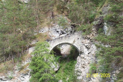 Römerbrücke von 180 nach Christus, die sich in Tirol bei der Ortschaft Tösens befindet. sie ist ein Teil der ehemaligen Straße nach Serfaus am Talhang über den Inn. Auf der westlichen Talseite hoch über der nach Untertösens führendenInnbrücke ist sie ein Stück der Via Claudia Augusta, die aus der Gegend um Tschuppbach über St. Georgen zur Hochfläche von Serfaus, Fiss und Ladis und von dort nach Pontlatz herabführte