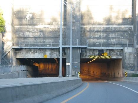 Vue agrandie au téléobjectif de l'entrée ouest du tunnel et de ses deux tubes de circulation. Remarquez à gauche, la piste cyclable qui est surélevée d'environ deux mètres par rapport à la chaussée