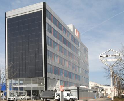 Die neue Fassade von Südosten: Im Süden die Photovoltaik-Module, im Osten gut zu erkennen die orangen Farbakzente der Schallschotts