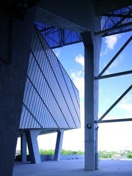 Zur Eingangsrampe hin öffnet sich das Stadiongebäude mit einer einladenden Geste nach oben. Die Deckenunterseite ist mit Titanzink in Winkelstehfalztechnik bekleidet.