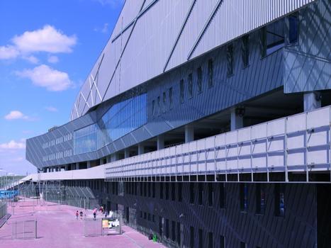 """Blick auf das fünfgeschossige Stadiongebäude. In der Mitte befindet sich die Promenade. In den beiden unteren Ebenen ist die Fassade mit Titanzink in der Oberflächenqualität """"vorbewittertpro schiefergrau"""" und in den beiden oberen Ebenen mit Titanzink """"vorbewittertpro blaugrau"""" bekleidet."""