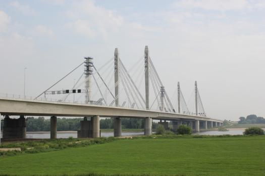 "The new and second Waal Bridge near Ewijk, enabling the traffic to flow in 4 lanes in each direction. To the left (behind) a pylon of the ""old"" bridge, where in near future Maurer will replace the expansion joints."