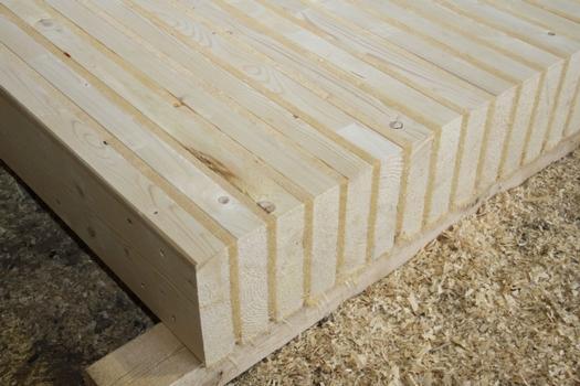 Systemdecke mit Sandwichprinzip: hochkant gestelltes Konstruktionsvollholz wird im Wechsel mit Holzfaserdämmplatten gestapelt und maschinell verschraubt.