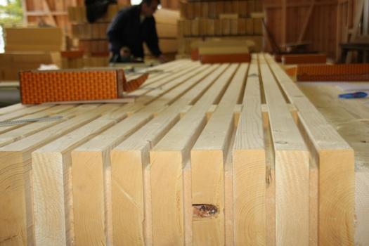 Das Konstruktionsvollholz wird im Wechsel mit Gutex-Holzfaserdämmplatten gestapelt.
