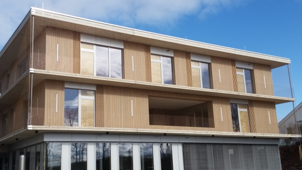 A row of floor-to-ceiling windows, broken up by elements made of exposed concrete, in the lower area contrasts with the façade cladding made of larch of the upper two floors.