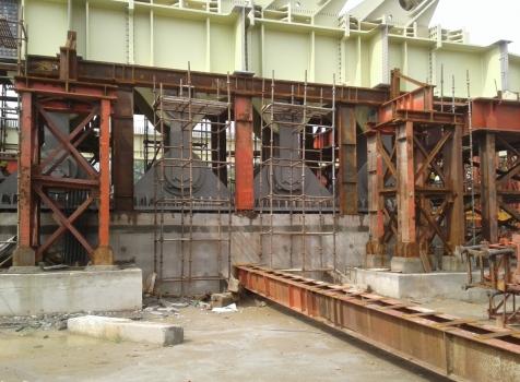 Die Pendellager (grau, Bildmitte) nehmen die Zugkräfte der Rückhalteseile auf (Verankerung am oberen rechten Bildrand erkennbar) und erlauben die Längsbewegung des Brückendecks (lindgrün).