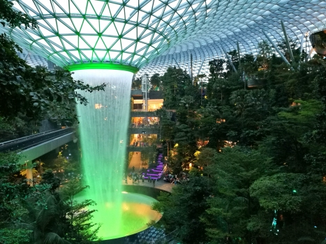 Jewel Changi Airport : The world's largest indoor waterfall drops 40 meters in the Jewel at Changi Airport. The waterfall and the roof and façade structures are supported pendulum supports (upper right of the picture). On the left you can see the railroad line of the airport express train.