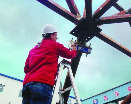 Ein Ingenieur prüft ein angeflanschtes Element zur thermischen Trennung, das am Stahlstützensystem montiert wurde, welches die EACF-Antarktisstation über dem gefrorenen Boden hält.