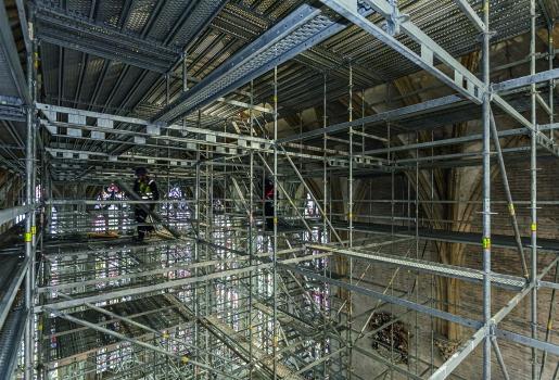 Im Gerüst wurden abgestufte Arbeitsebenen und Zugangsmöglichkeiten geschaffen, die eine sichere Ausführung der Arbeiten am Chorgewölbe und zeitgleich am Chorgestühl erlauben.