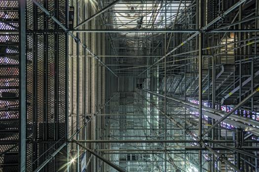 Der Zugang und der vertikale Materialtransport erfolgen über einen in die Gerüstkonstruktion integrierten Treppenturm sowie einen Bauaufzug.