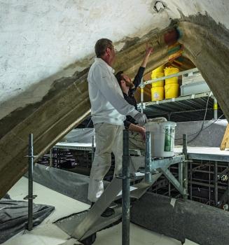 In 26 m Höhe wird die Gewölbedecke von Experten aufwendig per Hand saniert.