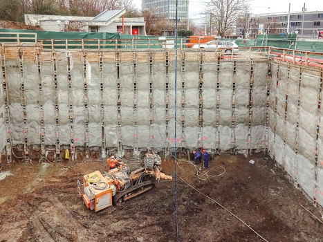 The excavation was built using a Berlin-type support system and tied back using strand anchors. : The excavation was built using a Berlin-type support system and tied back using strand anchors.