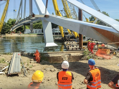 The largest, approximately 140 m long, 430 t element cantilevered over the river during construction before the gap was closed from the park side by the smaller element.