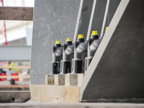 The post-tensioning bars pass through the pedestal, and protrude several feet above, so structural steel can be positioned onto the bars and they can still be stressed.