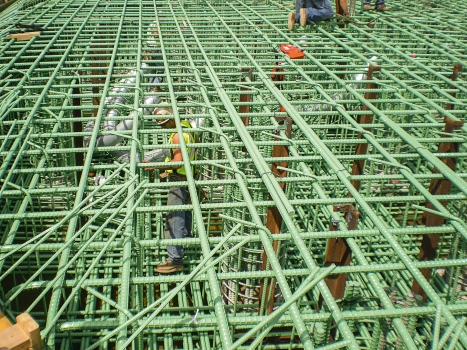 Prestressing ducts being laid in the reinforcing cage