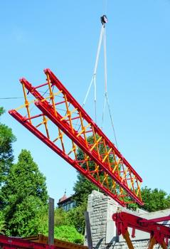 Modular shoring assembly: VARIOKIT system components were pre-assembled on the ground to form truss segments and placed into intermediate storage with the crane. Three such segments were subsequently coupled to create a 37 m long truss unit and lifted over the Mur by means of a mobile crane.