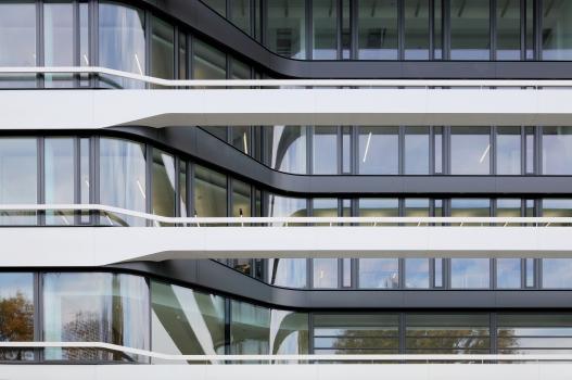 Im Eingangsbereich werden die beschichteten Fassadenbänder als stegartige Elemente vor der sich nach innen wölbenden Fassade fortgeführt.  : Im Eingangsbereich werden die beschichteten Fassadenbänder als stegartige Elemente vor der sich nach innen wölbenden Fassade fortgeführt.