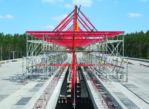 Die innenliegenden Gesimskappen der beiden getrennten Fahrbahnplatten wurden mit einer intelligent geplanten, fahrbaren Lösung effizient in Form gebracht: Beide Schalungen hingen an einer Konstruktion aus Variokit- und Peri Up-Systembauteilen, die sich auf der Brücke schnell verfahren ließ.