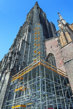 PERI UP schmiegt sich für die umfangreichen Sanierungsarbeiten bis auf 71 m Höhe an das Ulmer Münster, eine Zwischenplattform in 7 m Höhe dient als Lagermöglichkeit für die neuen Steine.