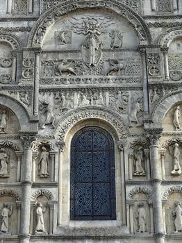 Angoulême - Cathédrale Saint-Pierre - Façade occidentale : partie centrale supérieure Thème de l'Ascension du Christ et annonce de la seconde venue du Christ En partie supérieure, le Christ apparaissant au milieu des nuées, encadré par les symboles des Evangélistes. En-dessous, quatre anges : les deux centraux gardent l'Arbre de Vie, les deux autres situés de part et d'autre montrent le Tétramorphe. Deux grands anges situés de part et d'autre du groupe central de quatre anges : celui de gauche penche la tête vers les spectateurs pour leur annoncer la Seconde Venue du Christ - celui de droite dont la tête a été refaite lève un bras pour montrer aux spectateurs le Christ