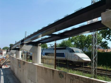 Montpellier - Viaduc Alphonse Loubat - Les piles encastrées dans le mur de soutènement des voies ferroviaires, les piles avec consoles, la charpente métallique avec passage d'un TGV à l'arrière