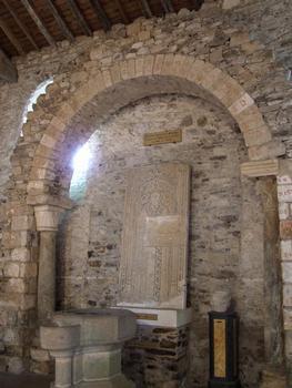 Saint-Philibert-de-Grand-Lieu - Abbatiale Saint-Philibert - Transept nord: arc roman qui se trouvait initialement en appui du grand arc gauche du carré du transept. Réutilisation de matériaux romains. Pierre tombale de Guillaume Chupin (15ème siècle)