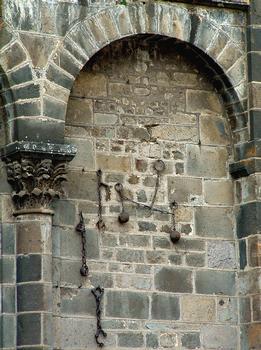 Orcival - Abbatiale - Chaînes déposées sur le mur de l'église