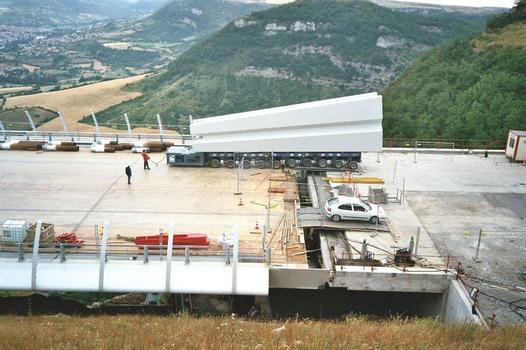 Millau-Viadukt  Der Pylonenkopf wird auf den Überbau mit einem ferngesteuerten Tieflader gefahren.