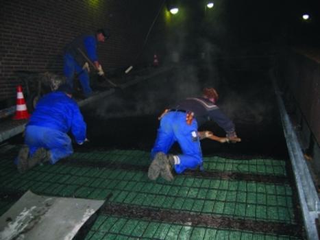 Verlegen der Gussasphaltdeckschicht auf einer Rampe mit elektrischer Rampenheizung bei Nacht