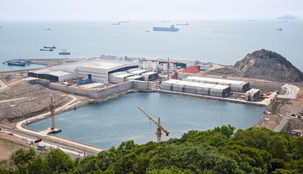 """Die fertigen Tunnelröhren mit 180 m Länge werden von der Feldfabrik in ein Trockendock verschoben, mit Schottwänden verschlossen und auf Meeresniveau abgesenkt. Beim Ausschwimmen stabilisieren Pontons die """"Fertigteile"""" während des Schleppvorgangs zur Absenkposition im südchinesischen Meer"""