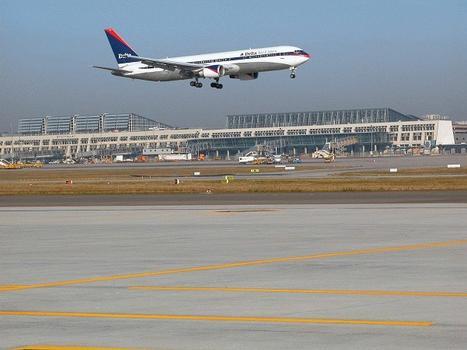 Flughafen Stuttgart  Landendes Flugzeug vor den Terminals 1 und 3.