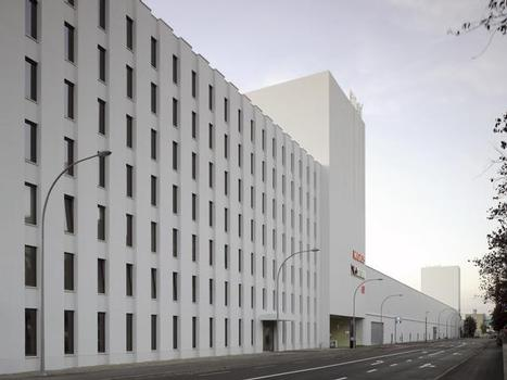 Dem Industrieareal gegenüber liegt im Osten die lange, reliefartig gegliederte Lochfassade des Hotels und der Büros