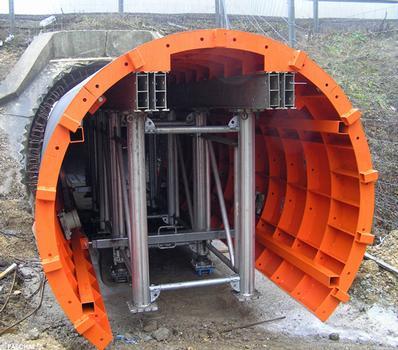 Nachdem die Schalung vor dem Tunnel zusammengebaut wurde, wird sie in den Tunnel gerollt. Unter dem GASS-Gerüst sind Lastroller befestigt, die es zu einem Schalwagen machen