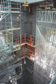 The sides of the cupola's supporting structure are supported during the construction work by scaffoldings measuring up to heights of 23.8 m. In the corners, L-shaped concrete pillars rise upwards