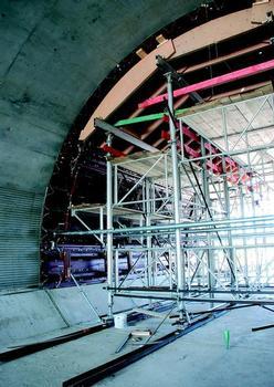 Betoninnenseite: Der Schalwagen mit dem GASS-Gerüst trägt die liegende Tunnelschalung aus mehreren 3,00 m hohen Segmenten der radienverstellbaren Trapezträger-Rundschalung; die Streifen im Beton über der Innenvoute rühren von der formenden Einlage her