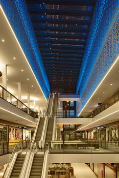 Die Größe des Raumes wird durch die Rolltreppe, die alle Ebenen miteinander verbinden, verstärkt