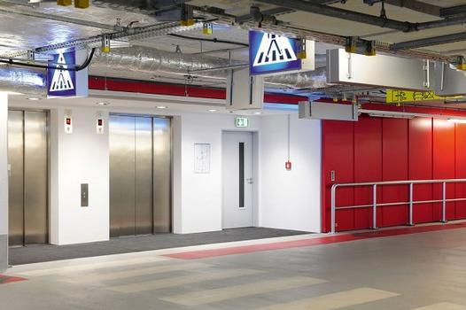 """In der Tiefgarage sorgen farbig lackierte Schiebetore für den Brandschutz. Das Bild zeigt ein T90-Tor """"Teckentrup E"""", das im Brandfall den gesamten Erschließungsweg – Fahrstühle und Treppenhaus – sichert"""