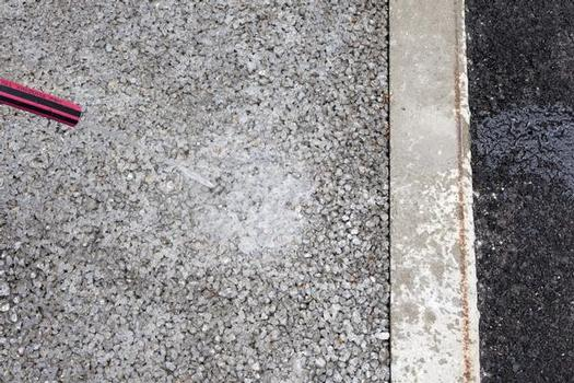Dränbeton-Testfläche: Während sich das Wasser auf normalem Beton oder Asphalt staut und nur langsam abfließt (rechts im Bild), kann es auf dem neuen Dränbeton einfach und schnell versickern (links)