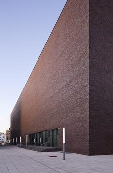 Dicht aneinandergereihte, schlanke Lichtstelen erhellen mit ihrem weit sichtbaren Eigenlicht die Gebäudeschlucht zwischen dem Kulturquartier und der benachbarten Bebauung