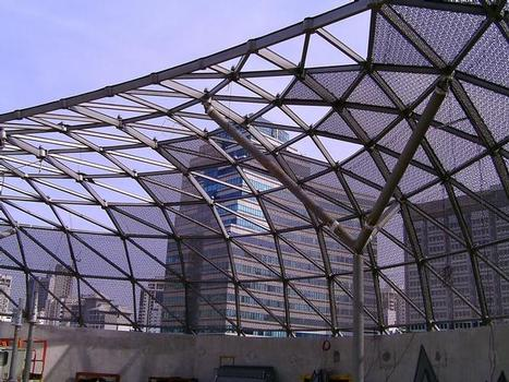 The irregular wave shape of the main canopy spans the public space in front of the building