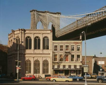 Brooklyn Bridge: View of Brooklyn tower emerging behind nineteenth century commercial buildings on the corner of front street and Camden plaza   (HAER, NY,31-NEYO,90-80)
