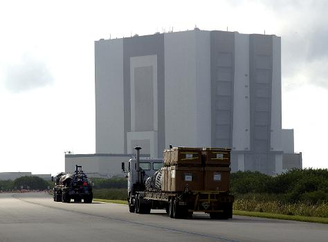 Flatbed trucks carrying some of the debris of Space Shuttle Columbia approach the Vehicle Assembly Building (VAB). The debris is being transferred from the Columbia Debris Hangar to the VAB for permanent storage. More than 83,000 pieces of debris were shipped to KSC during search and recovery efforts in East Texas. That represents about 38 percent of the dry weight of Columbia, equaling almost 85,000 pounds.  Source: NASA Photo Number: KSC-03PD-2613.